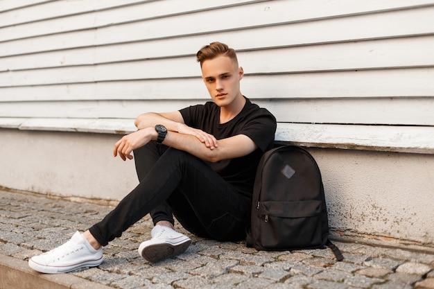 Giovane sveglio in una maglietta nera in jeans neri alla moda in scarpe da ginnastica alla moda con uno zaino sportivo nero sta riposando seduto sull'asfalto vicino a un edificio vintage in legno bianco