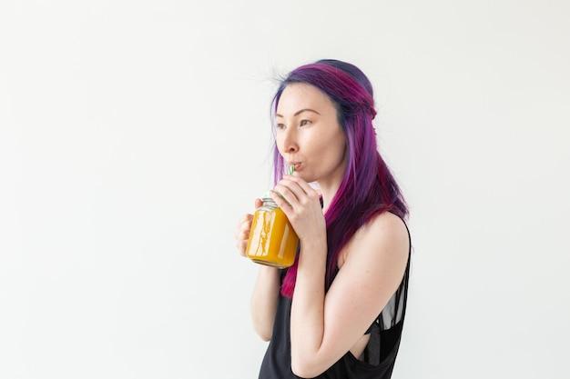 Carina giovane ragazza hipster di razza mista con capelli colorati beve frullato di frutta prima di iniziare uno yoga