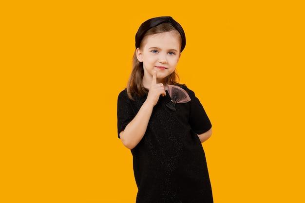Ragazza carina giovane modella in abito di tulle nero retrò e fascia per capelli che tocca il mento