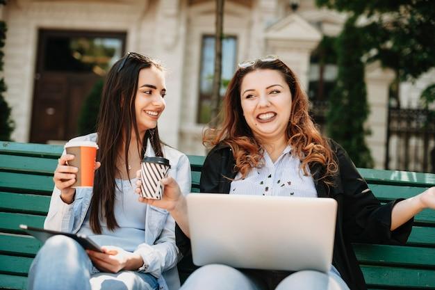 Carine giovani donne plus size che raccontano storie tenendo un laptop sulle gambe e una tazza di caffè in una mano mentre la sua amica la guarda sorridendo.