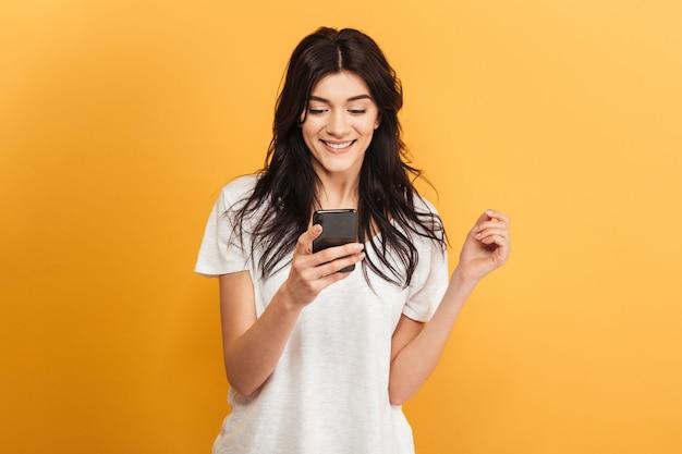 Giovane donna graziosa sveglia che chiacchiera dal telefono cellulare.