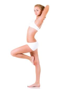 Carina giovane ragazza sottile in lingerie bianca in posa su una