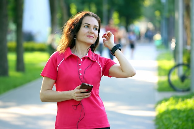 Carina giovane donna sportiva che ascolta la musica in una passeggiata
