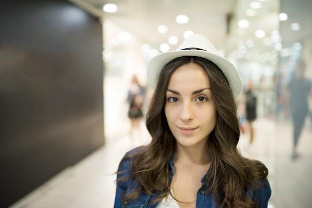 La giovane donna alla moda sveglia in un cappello sta camminando sul centro commerciale durante lo shopping