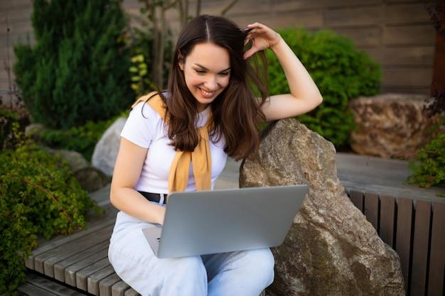 Carina giovane donna che beve il caffè si siede su una panchina con un computer portatile per strada.