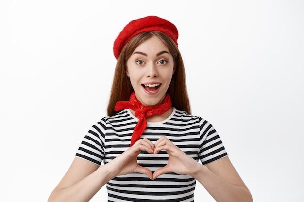 Carina giovane donna in berretto francese, che mostra il segno del cuore e sorride con stupore, dire ti amo, in piedi sul muro bianco