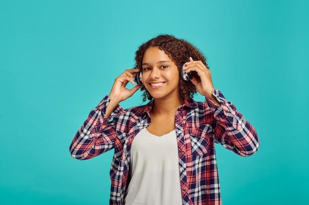 Carina giovane donna in cuffie, parete blu, emozione positiva