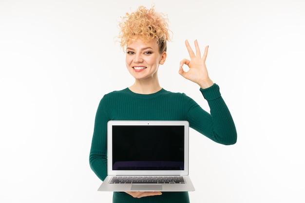 La giovane donna sveglia tiene il computer con il modello con lo schermo in avanti su bianco