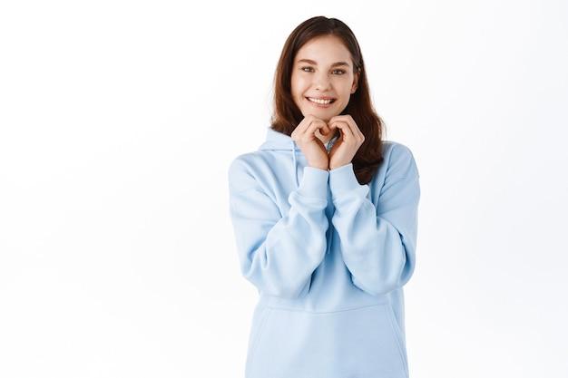 Carina giovane donna in felpa con cappuccio, che mostra il gesto del cuore della mano e ti sorride, amore e segno simile, in piedi contro il muro bianco