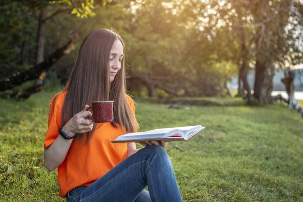 Una giovane donna carina con una maglietta arancione è seduta sull'erba verde della foresta con una tazza di tè e un libro. concetto di un piacevole passatempo, riposo, relax, stile di vita