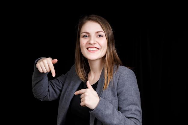 Una giovane donna carina che punta verso il basso con due dita