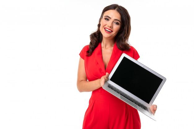 La giovane donna sveglia in vestito rosso tiene il taccuino con il modello con lo schermo in avanti su bianco