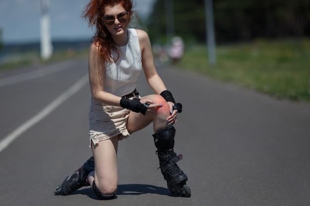 Carina giovane donna in abiti estivi è caduta sulla strada e mostra il ginocchio contuso durante il pattinaggio a rotelle