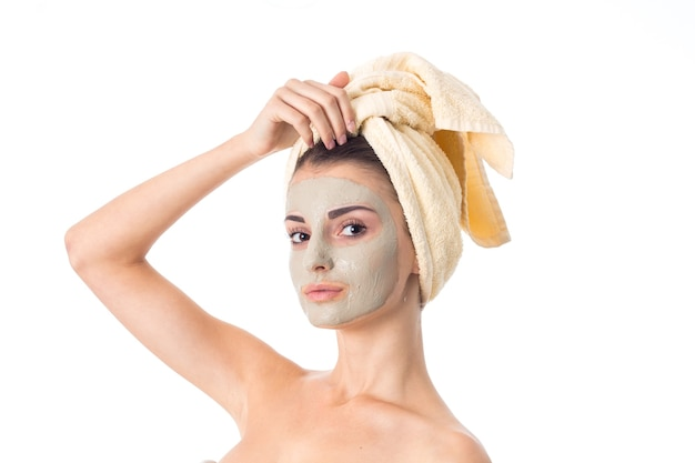 La giovane donna sveglia si prende cura della sua pelle con maschera detergente sul viso e asciugamano sulla testa isolata sul muro bianco