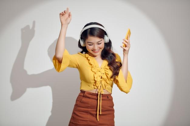 Giovane donna sveglia che texting sul suo telefono mentre ascolta la musica