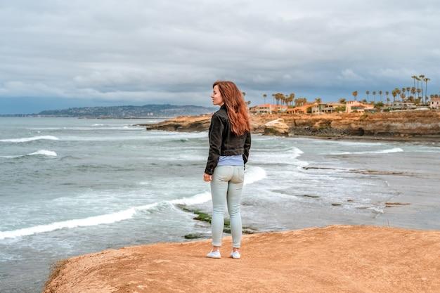 Una giovane donna carina cammina lungo l'oceano pacifico al parco naturale delle scogliere al tramonto a san diego