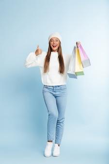 Carina giovane donna che indossa il cappello invernale, tenendo le borse della spesa.