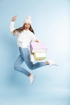 Carina giovane donna che indossa il cappello invernale che salta, tenendo i sacchetti della holding.
