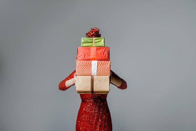 Carina giovane donna con il cappello di babbo natale che nasconde il viso dietro una confezione regalo blu.