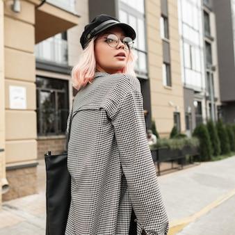 Carina giovane donna con occhiali eleganti e cappello vintage con camicia casual alla moda che cammina per strada vicino all'edificio