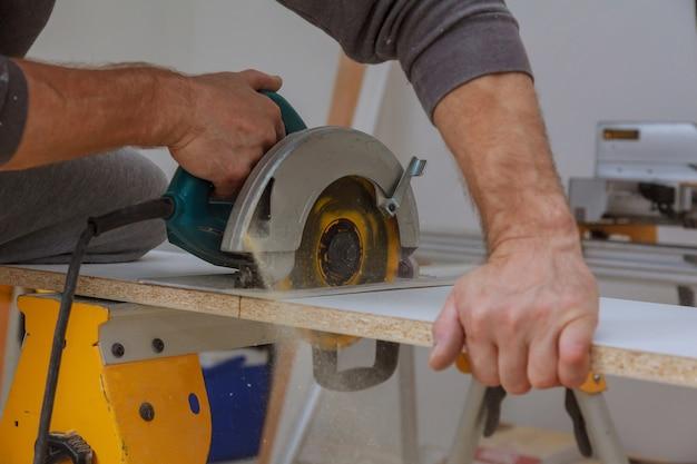Sega elettrica cuthand per il taglio di ripiani in legno laminato bianco