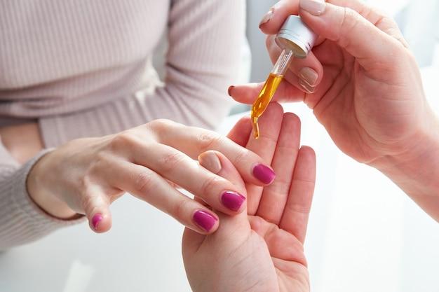 Cura delle cuticole. mano femminile che applica olio sulle unghie