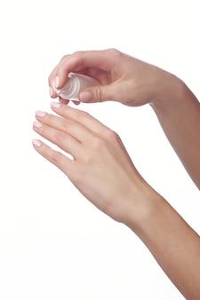 Olio per cuticole. manicure e spa mani. primo piano delle mani della donna
