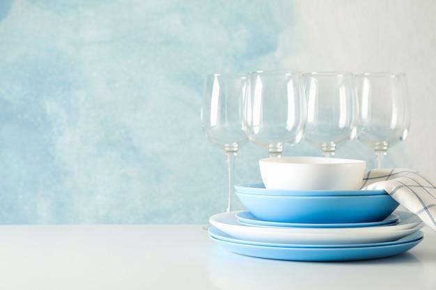 Coltelleria meravigliosamente impilata sulla tavola bianca contro la tavola blu