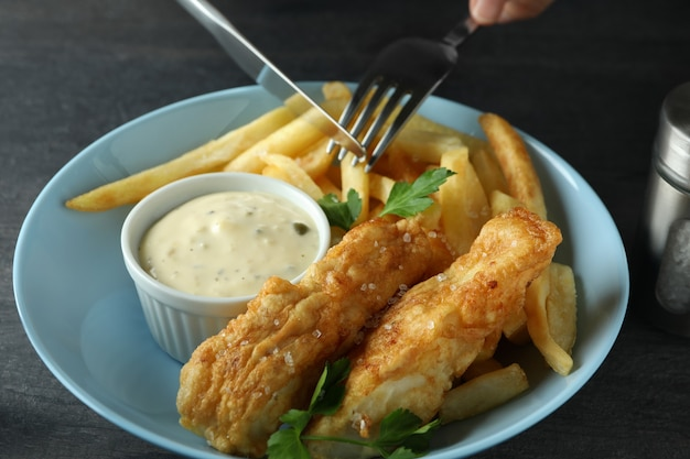 Posate sopra il pesce fritto e patatine fritte, da vicino