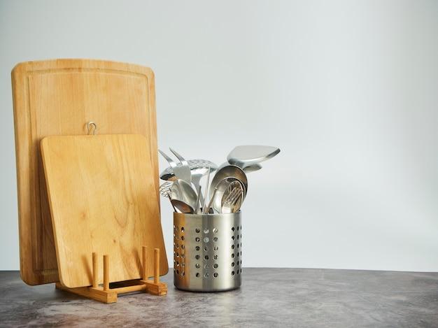 Portaposate, taglieri in acciaio inox e legno su tavola