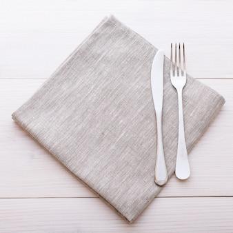 Coltelleria e tovaglia sulla tavola di legno bianca