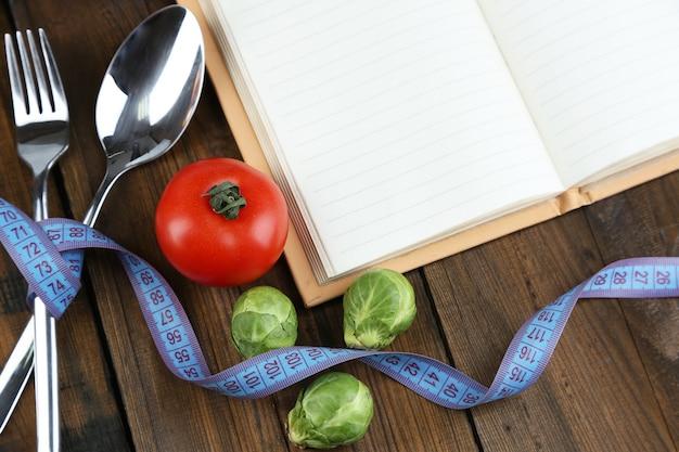 Posate legate con metro a nastro e libro con verdure su tavola di legno