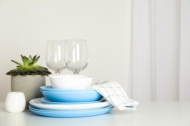 Coltelleria con la pianta succulente impilata sulla tavola bianca