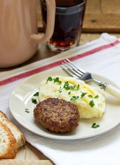 Cotoletta, purè di patate con burro e prezzemolo e tè su un tavolo di legno.
