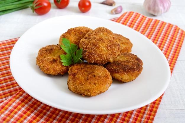 Cotolette. cotolette succose della carne su un piatto bianco su un fondo di legno.