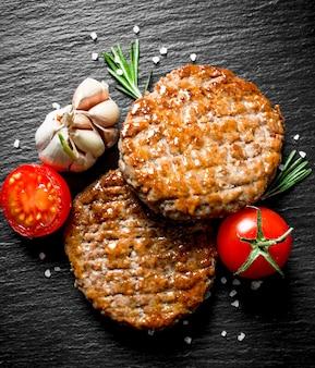 Cotolette con pomodoro, aglio e rosmarino. su sfondo nero rustico