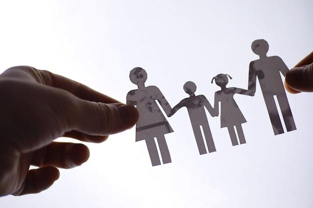 Famiglia di catene di carta ritagliata con protezione delle mani a coppa, concetto di sicurezza e cura. mani con sagoma di carta ritagliata sul tavolo. concetto di cura della famiglia