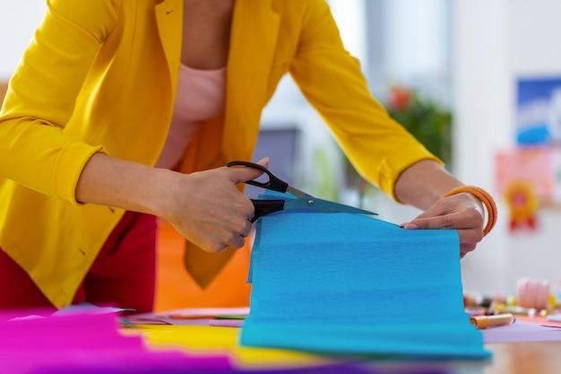 Taglio carta blu. insegnante di scuola elementare che indossa una giacca gialla che taglia carta blu per i suoi alunni