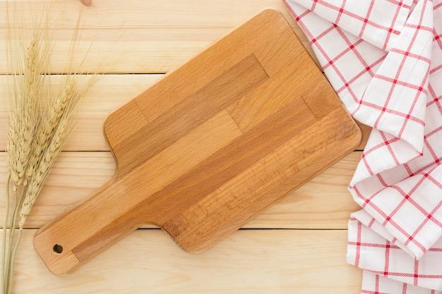 Tagliere, orecchio di risone e tovagliolo sullo sfondo in legno
