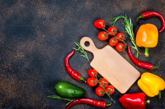 Tagliere, verdure fresche, spezie, erbe e ingredienti sani su sfondo scuro vista dall'alto