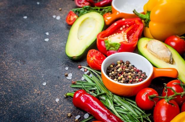 Tagliere, verdure fresche, spezie, erbe aromatiche e ingredienti sani su sfondo scuro