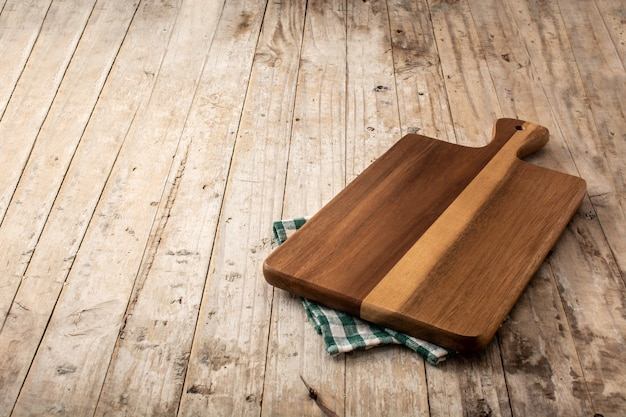 Mockup di tagliere e tovaglia verde sulla tavola di legno