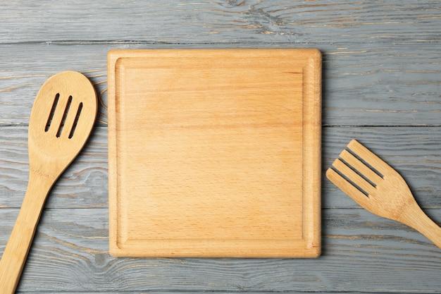 Tagliere, cucchiaio e forchetta su fondo in legno