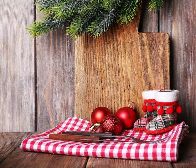 Tagliere con decorazioni natalizie su sfondo di assi di legno