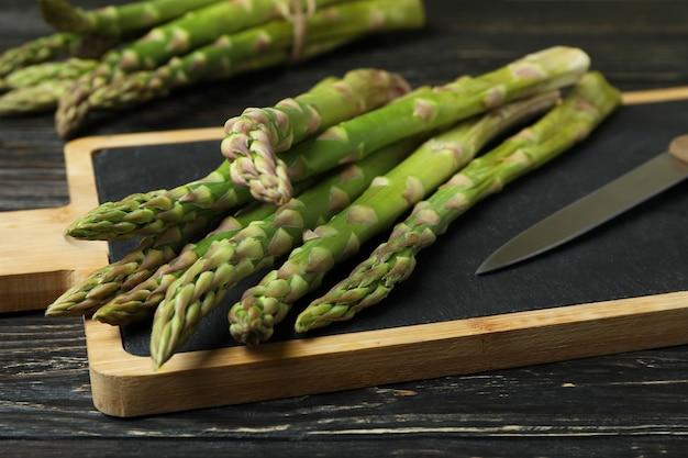 Tagliere con asparagi verdi su fondo in legno