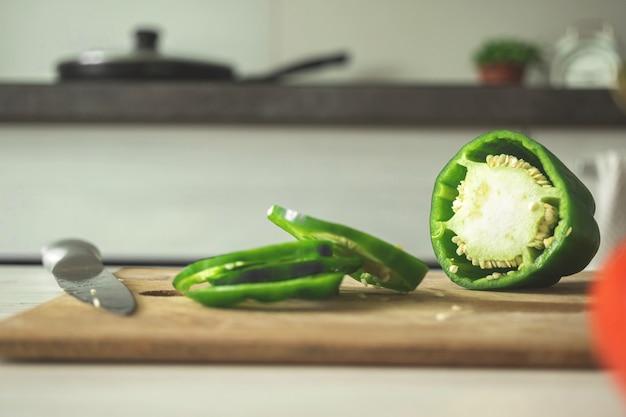 Tagliere con peperoni dolci verdi su uno sfondo di cucina moderna. peperoni a fette su tavola di legno. ingrediente vegetale, cucinare cibo sano concetto foto