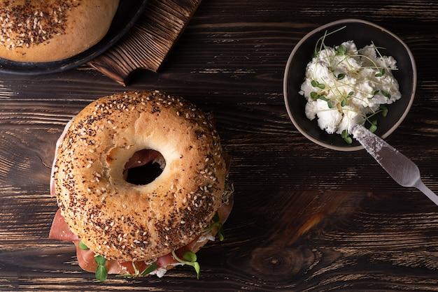 Tagliere con bagel prosciutto e ricotta su fondo in legno scuro, panino prosciutto e formaggio, stile rustico.