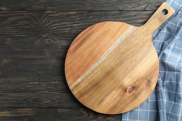 Tagliere con l'asciugamano di cucina su fondo di legno, spazio per testo