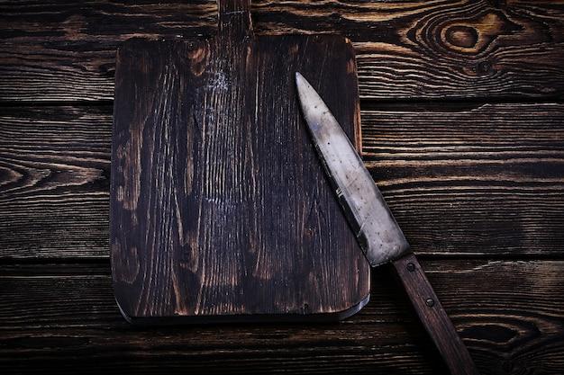 Tagliere con un coltello su fondo di legno vecchio