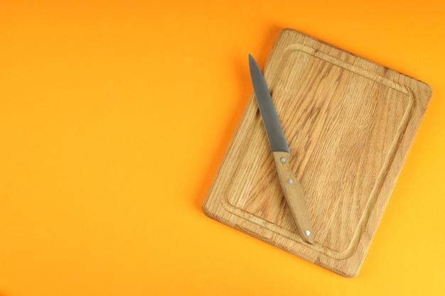 Tagliere con coltello su sfondo arancione.